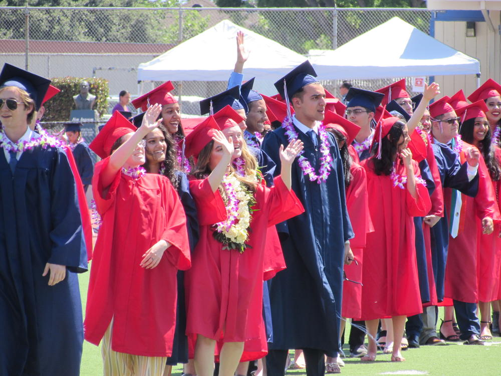 American seniors wave to the crowd at graduation ceremony.