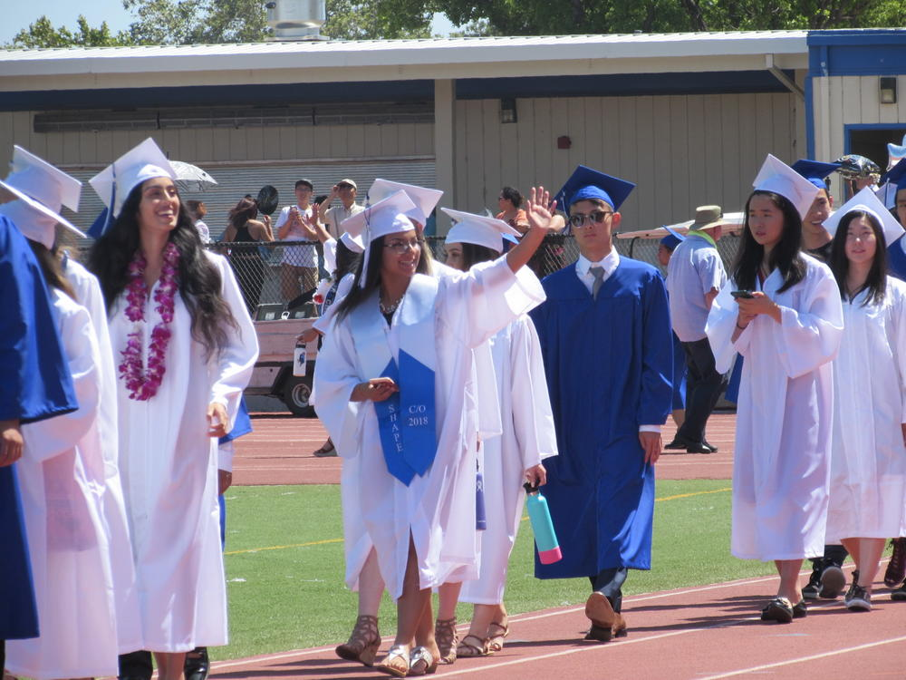 Irvington High School grad waves to family at 2018 graduation ceremony.
