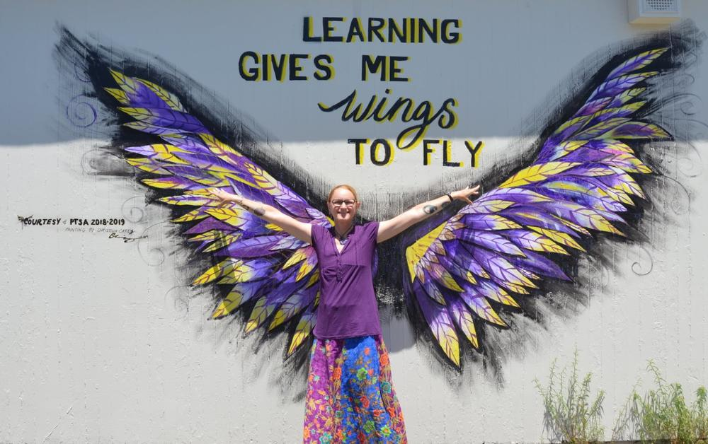 Walters teacher poses by new mural.