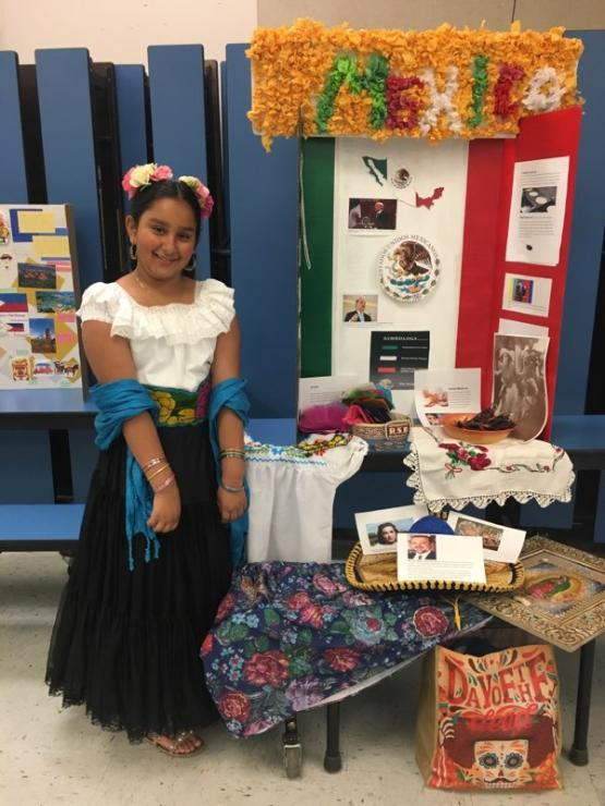 Millard student poses by her Mexico display.