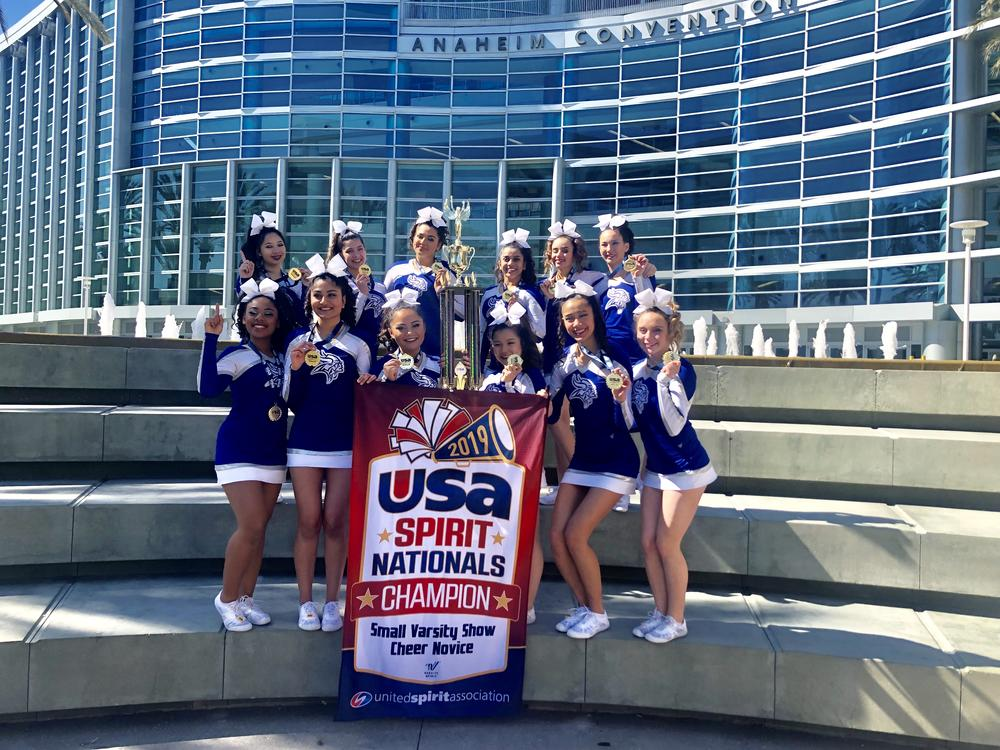 Irvington Cheer pose with championship banner in Anaheim.
