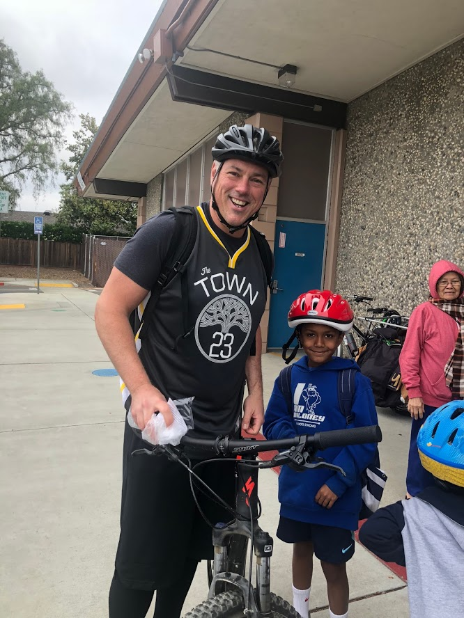 Maloney Principal Chris Wood and student ride to school for Bike to School Day.