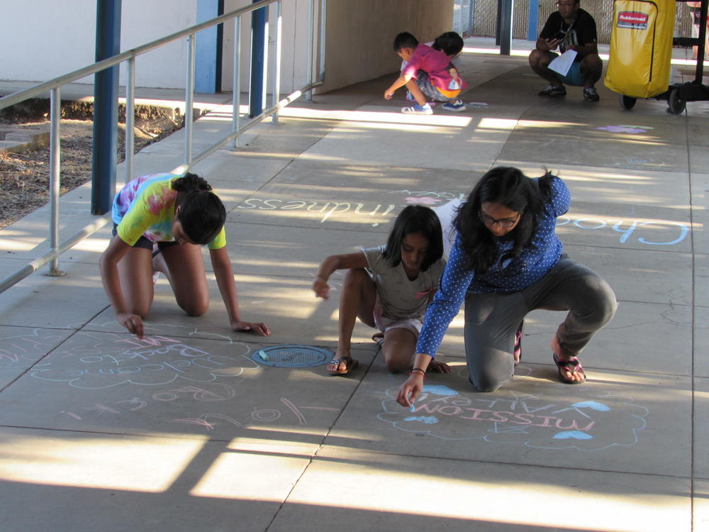 Mission Valley students and family work on chalk art display.